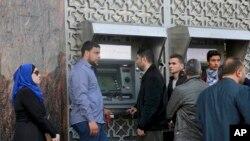 گروهی از مردم در مقابل دستگاه پرداخت پول بانک در شهر غزه