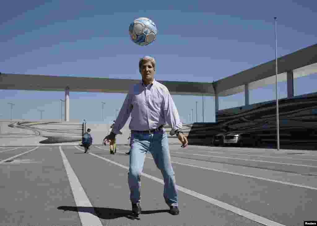 파키스탄에 이어 영국 방문을 앞둔 존 케리 미국 국무장관이 중간 급유를 위해 기착한 오스트리아 비엔나 공항에서 국무부 직원들과 축구를 하고 있다.