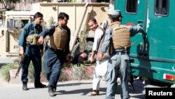 Афганські поліцейські несуть тіло загиблого товариша