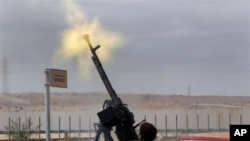 An anti-Gadhafi rebel fires on a government warplane flying overhead in Ras Lanouf, eastern Libya, March 9, 2011