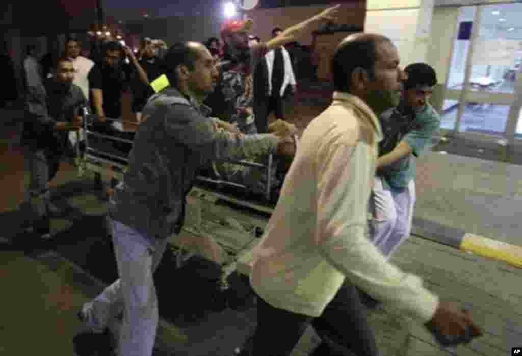 Bahrainis rush a wounded anti-regime protester into a hospital in Manama, February 18, 2011, after police opened fire on opposition protesters, wounding dozens of them. (AFP Image)