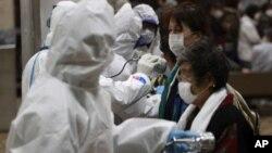 Ana auna mutanen da aka kwashe daga kusa da masana'antar nukiliya ta Fukushima domin a ga ko alamar tururi mai guba a jikinsu, talata 15 Maris 2011.