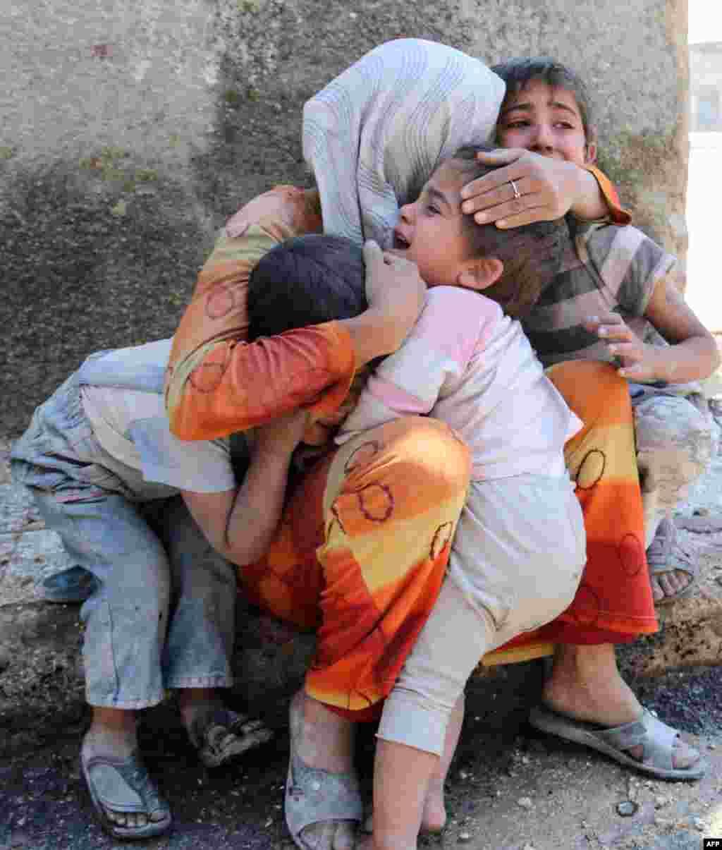시리아 북부 알레포 시에서 폭탄테러가 발생한 후, 겁에 질린 아이들이 엄마 품에 안겨 울고 있다.