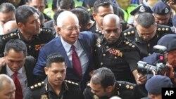တရားရင္ဆိုင္ဖုိ႔ တရား႐ုံးလာေရာက္သူ Najib Razak (အလယ္)