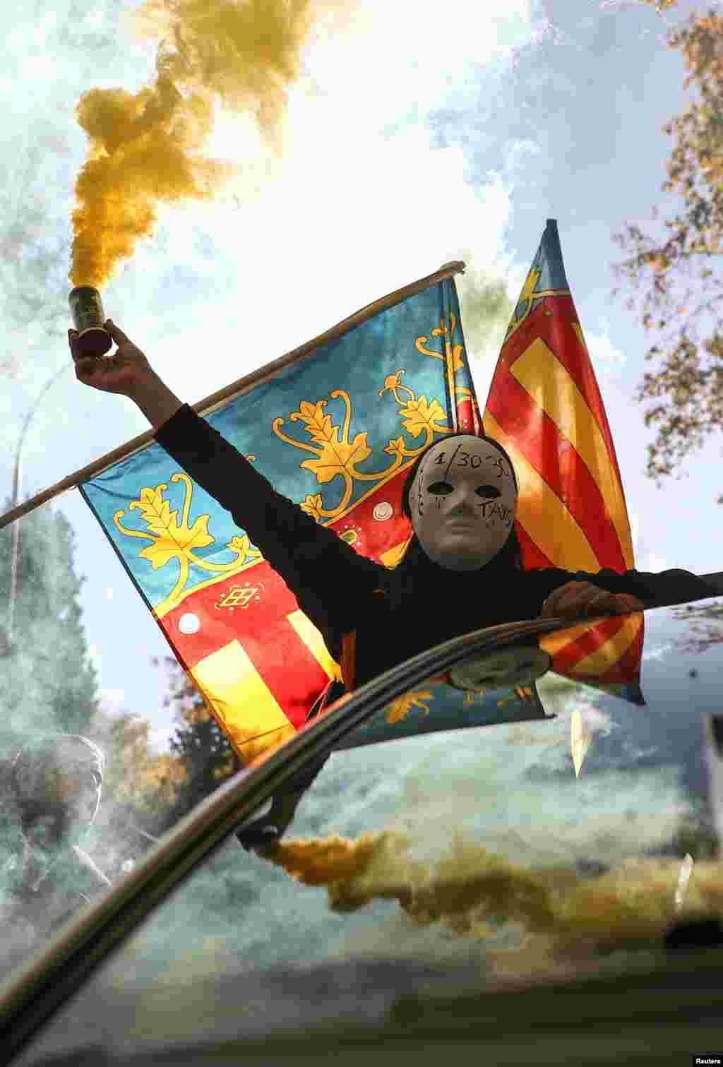 شرکت یک معترض ماسک پوش با نارنجک دودزا در دستش در تظاهرات مادرید اسپانیا بر علیه شرکت های خصوصی مسافربری از جمله اوبر