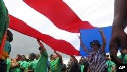 Puertorriqueños levantan una bandera de su isla durante una protesta el Primero de Mayo contra inminentes medidas de austeridad en medio de una agobiante crisis económica.