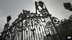 Рабочий поправляет фонарь на воротах, ведущих к зданию Народной ассамблеи Египта (архивное фото)