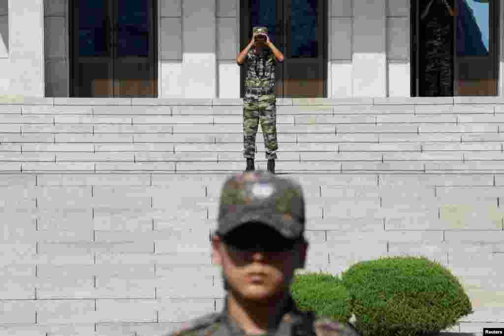 A North Korean soldier looks toward the south as a South Korean soldier stands guard in the truce village of Panmunjom inside the Demilitarized Zone separating the two Koreas, South Korea.