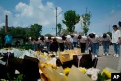 河南鄭州市民在地鐵5號線站台前給洪災死難者獻上鮮花,鞠躬致哀。(2021年7月27日)