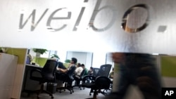 Employees work at their desks at a Sina Weibo office in Beijing's leading microblog site, (File photo).