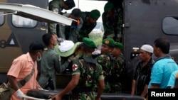 Para prajurit mengeluarkan jenasah prajurit korban serangan kelompok sipil bersenjata, setibanya di bandara Sentani, Papua (22/2/2013)