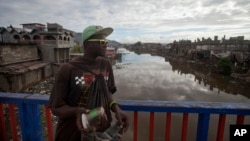 Venel Ceus 29, a street vendor stands against the bridge of a canal in Cap Haitien, Haiti, April 1, 2015. Many Haitians are not eager to see the development of mining, skeptical of an industry that could pollute a country with a history of weak regulation and environmental problems.