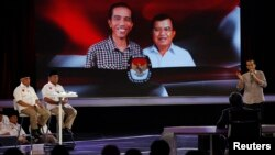 "Indonesian presidential candidate Joko ""Jokowi"" Widodo (R) speaks during a debate on television with his opponent Prabowo Subianto and Hatta Rajasa (L) in Jakarta, July 5, 2014."