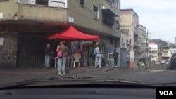 """Un punto rojo del oficialismo, donde los electores venezolanos de escasos recursos que votaron este domingo, escaneaban el """"carnet de la patria"""" con la esperanza de recibir """"un premio"""" que les ofreció el presidente Nicolás Maduro. Foto: Fabiana Rondón, VOA. Mayo 20 de 2018."""