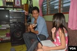 Ông bố Rodrigo Wage chơi một khúc nhạc cho đứa con gái 8 tuổi sau một ngày dài làm việc nhà. (Ảnh: Simone Orendain/VOA)