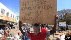 FILE: Vendors hold placards written in the local language, Shona, saying they will not move after they were removed from the streets of Harare, Wednesday, July, 8, 2015. (AP Photo/Tsvangirayi Mukwazhi)