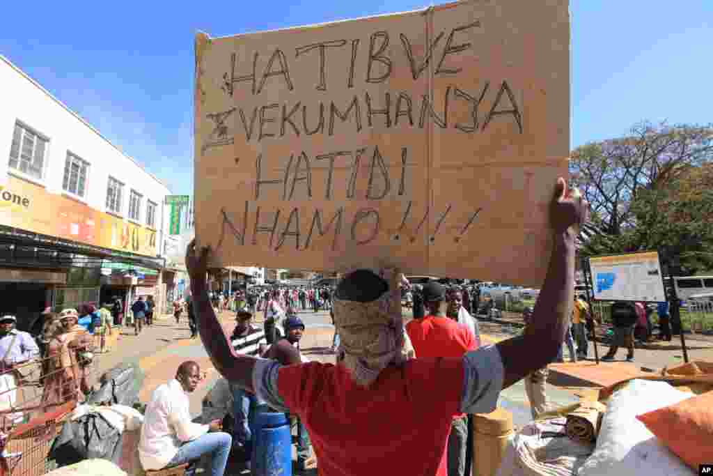 Vendors hold placards written in the local language, shona, saying they will not move after they were removed from the streets of Harare, Wednesday, July, 8, 2015. Minor scuffles ensued as police officers drove out thousands of vendors selling their wares on the sidewalks and pavements of Harare.
