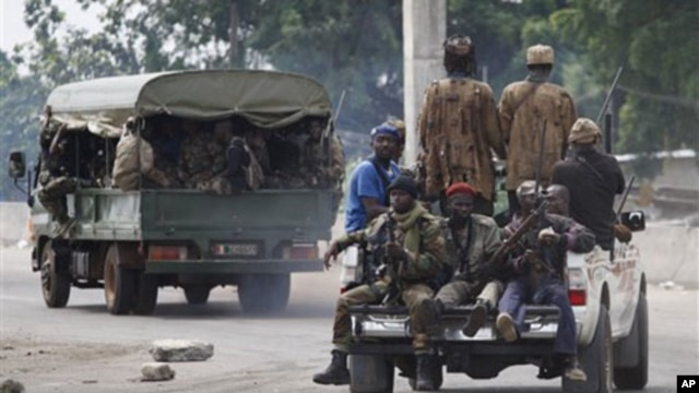 Soldiers loyal to Alassane Ouattara head off for battle as they deploy from a checkpoint at one of the principal entrances to Abidjan, Ivory Coast, Wednesday, April 6, 2011.