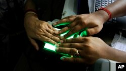 FILE- An operator helps an elderly woman scan her fingerprints as she enrolls for Aadhar, India's unique identification project in Kolkata, India, May 16, 2012. India's top court has ruled that the right to privacy is a fundamental right of every citizen