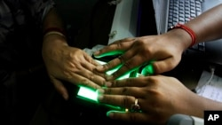 FILE - An operator helps an elderly woman scan her fingerprints as she enrolls for Aadhar, India's unique identification project in Kolkata, India, May 16, 2012. India's top court has ruled that the right to privacy is a fundamental right of every citizen of the country.
