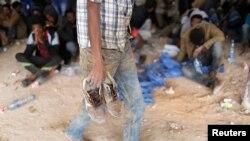 Un migrant africain tient ses chaussures en main après avoir été détenu à Zaouïa, au nord de la Libye, le 1er juin 2014.