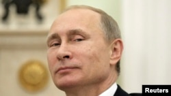 FILE - Russian President Vladimir Putin, shown in 2014, plans to address the U.N. General Assembly on Sept. 28, 2015. His country has ramped up its military presence in Syria.