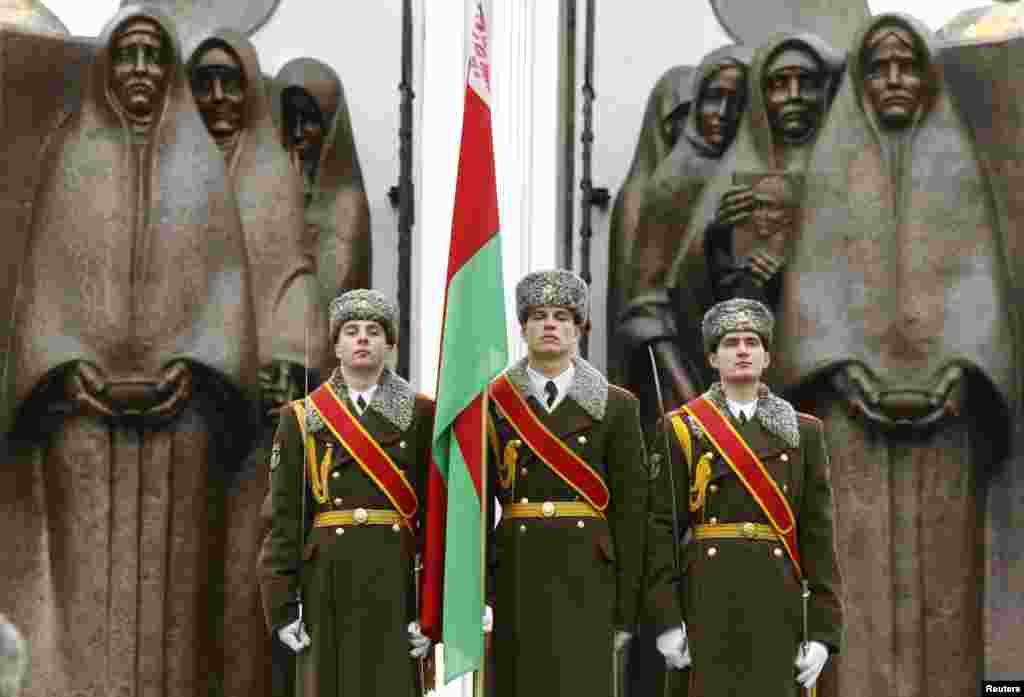 Honor guards stand near a monument in Minsk, Belarus, commemorating the Soviet victims of the war in Afghanistan, along with many former Soviet states, marked the 25th anniversary of the Soviet troops' withdrawal from Afghanistan where they fought for more than nine years.