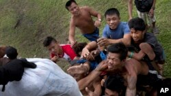 Dân làng bị mắc kẹt bởi cơn bão Haiyan tranh nhau nhận cứu trợ từ trực thăng Sea Hawk của hải quân Mỹ tại thị trấn ven biển Tanawan, Philippines, ngày 17/11/2013.
