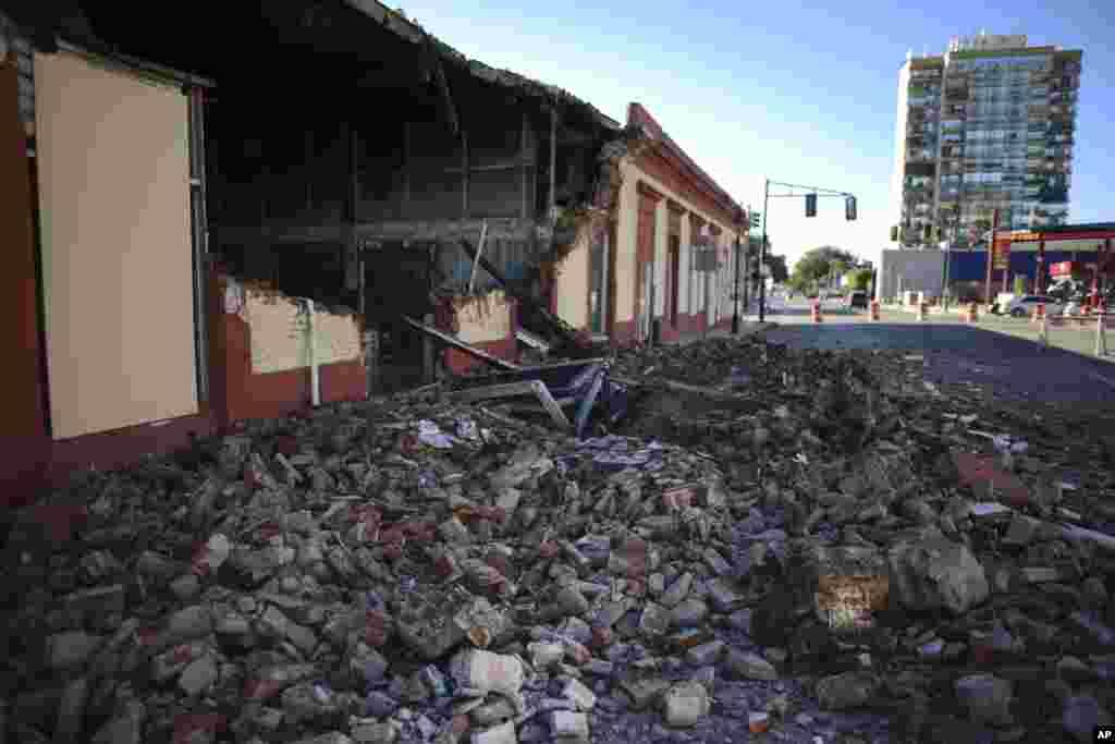 Los escombros de una pared derrumbada de un edificio cubren el suelo, en Ponce.