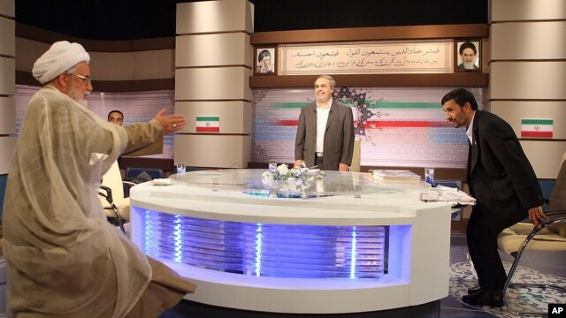 In this photo released by Islamic Republic of Iranian Broadcasting, Iranian presidential candidate, Mahdi Karroubi, left, arrives to attend a debate with Iran's President Mahmoud Ahmadinejad, right, during a debate in Tehran, June, 6, 2009.