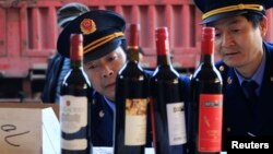 Police officers check bottles of confiscated fake wines before destroying them in Xi'an, Shaanxi province Jan. 4, 2012.
