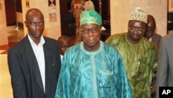 Former Nigerian President Olusegun Obasanjo, center, leaves his hotel for a meeting with incumbent Ivorian President Laurent Gbagbo in Abidjan, Ivory Coast, 08 Jan 2011