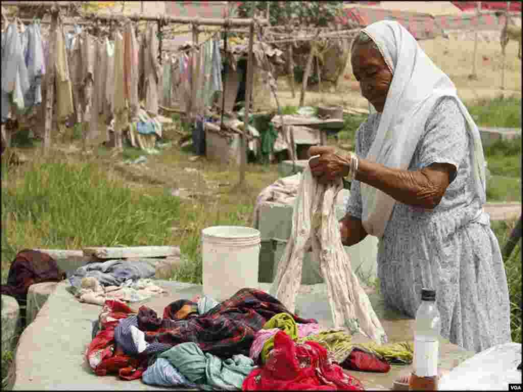 کراچی کے دھوبی گھاٹ میں ایک عمر رسیدہ خاتون کپڑے دھو رہی ہیں۔