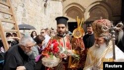 Le Patriarche grec orthodoxe de Jérusalem Metropolitan Theophilos ( R ) plonge des fleurs dans l'eau avant de bénir la foule pendant le lavage de la cérémonie de remise des pieds hors de l'Eglise du Saint-Sépulcre , dans la vieille ville de Jérusalem , le 17 Avril 2014.( Archives)