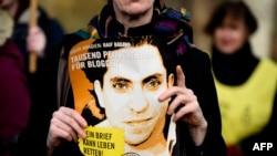 تصویر رائف بداوی وبلاگ نویس عربستانی، که از سال گذشته در عربستان سعودی زندانی است، در دستان یک فعال حقوق بشر در برلین آلمان - آرشیو