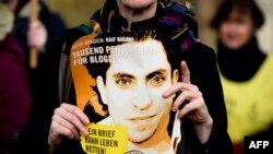 Seorang aktivis kelompok HAM 'Amnesty International' membawa foto blogger Saudi Raif Badawi dalam protes menuntut pembebasan Badawi di depan Kedubes Saudi di Berlin, Jerman (foto: dok).