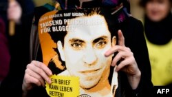 FILE - An Amnesty International activist holds a picture of Saudi blogger Raif Badawi during a protest against his flogging punishment, in front of Saudi Arabia's embassy in Berlin, Germany, Jan. 29, 2015.