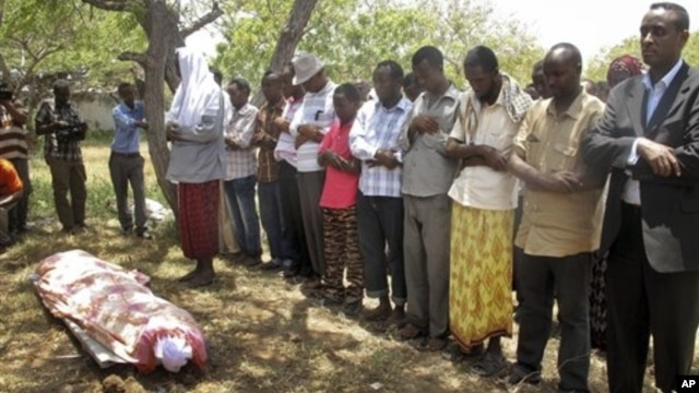 Mourners attend the funeral for Abdisatar Dahir Sabriye, a journalist with state-run television who fell victim to a recent suicide bombing, Mogadishu, Sept. 21, 2012.