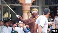 Algojo pelaksana cambuk mengayunkan rotan ke punggung pelanggar hukum syariah di Banda Aceh (19/9). (VOA/Budi Nahaba)