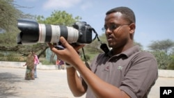 FILE - Somali journalist Mohamed Mohamud holds his camera in the Medina hospital compound in Mogadishu, Somalia, Jan. 18, 2013. Mohamud was killed on the job in 2013.
