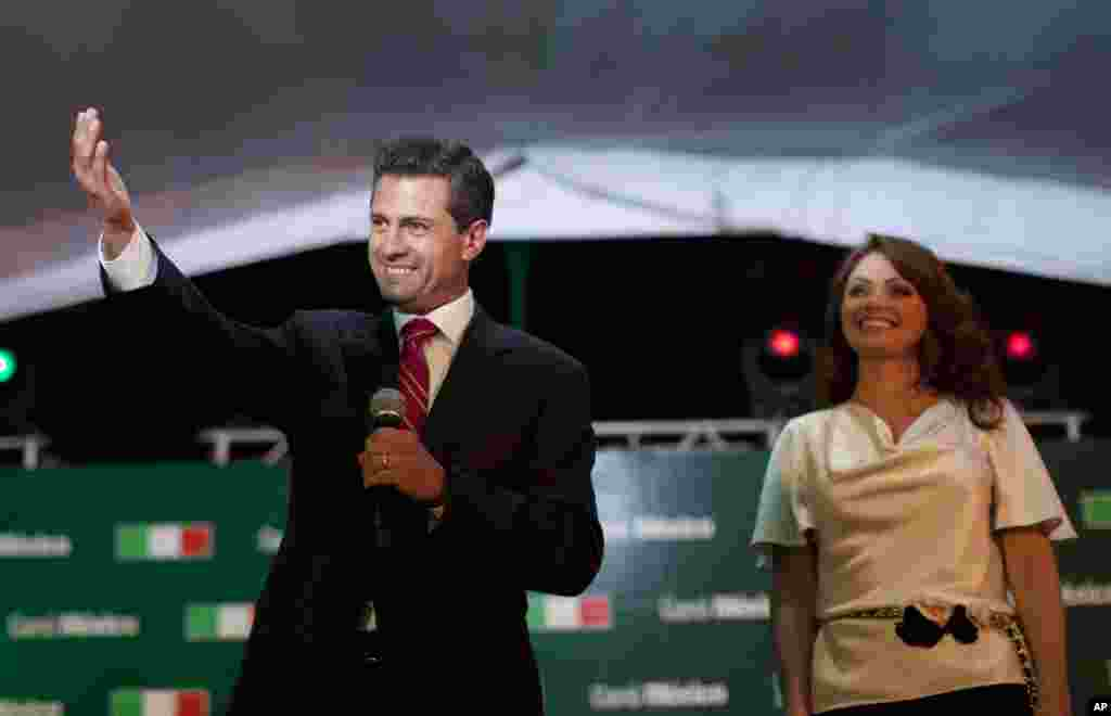 Enrique Pena Nieto, presidential candidate for the Revolutionary Institutional Party (PRI), left, speaks to supporters accompanied by his wife Angelica Rivera at the party's headquarters in Mexico City, early Monday, July 2, 2012.