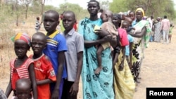 File - Residents displaced due to the fighting between government and rebel forces in the Upper Nile capital Malakal wait at a World Food Program outpost.
