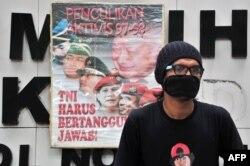 """Seorang pengunjuk rasa duduk di samping spanduk yang bertuliskan """"Penculikan Aktivis 1997-1998, TNI Harus Bertanggung Jawab"""" saat melakukan protes terhadap Prabowo Subianto di Jakarta, 20 Mei 2014. (Foto: dok)."""
