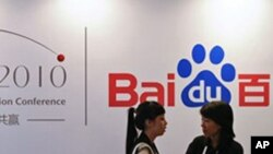 In this Sept. 2, 2010, file photo, a Baidu employee, right, chats with a visitor during the Baidu Technology Innovation Conference held in Beijing, China.