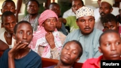FILE - Men, part of the 70 arrested during a police raid on a mosque, sit in a court in Shanzu, Feb. 12, 2014.