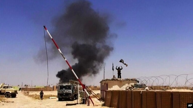 An image posted on a militant news Twitter account, June 12, 2014, shows militants from the al-Qaida-inspired Islamic State of Iraq and the Levant (ISIL) people raising their flag at the entrance of an army base in Ninevah Province.