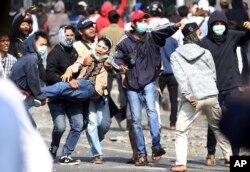 Massa pendukung capres Prabowo Subianto menggotong seorang pria yang terluka dalam bentrokan dengan aparat kepolisian di Jakarta, 22 Mei 2019.