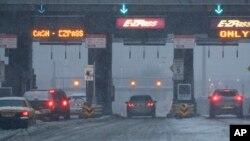 Des voitures attendent au péage d'un pont sous la neige dans le New Jersey, le 9 février 2017.