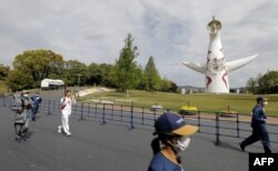 Mantan perenang gaya punggung Jepang Aya Terakawa membawa obor Olimpiade Tokyo 2020 dalam estafet obor Olimpiade di Taman Peringatan Expo '70 di Suita, prefektur Osaka, 13 April 2021.