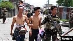 Tentara Pemerintah Filipina mendampingi warga yang disandera dan dijadikan 'tameng manusia' oleh para pemberontak muslim di kota Zamboanga, Filipina (17/9).